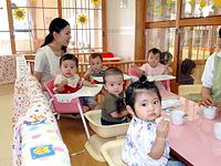 こどもたちがご飯を食べている様子。保育士がこどもたちを見ている。
